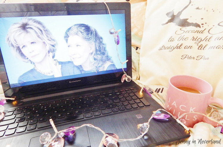 Laptop showing Grace and Frankie, resting on a bed with fairy lights and a cup of tea in a Jack Wills mug